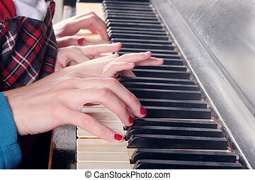 Hands of two people playing the piano.