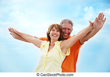 Mature couple with arms outstretched over a blue sky...