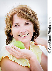 Beautiful mature woman holding an apple - Close-up portrait...