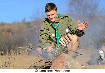 Boy Scout Cooking Sausages on Stick over Campfire - Boy...