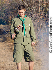 Boy Scout with Stick of Sausages by Campfire - Boy Scout...