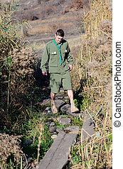 Boy Scout Crossing Creek on Wood Plank Footbridge - Full...