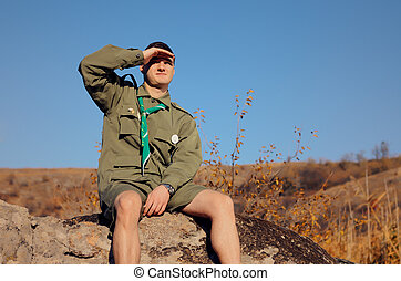 Boy Scout Sitting on Rock Watching Over the Field - Young...