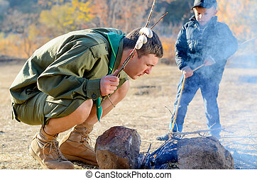 Boy Scout with Sausages on Stick by Campfire - Boy Scout in...