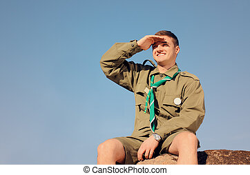 Boy Scout Sitting on Rock Watching Over the Field