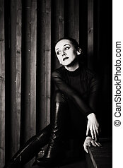 young woman sitting on wooden stairs