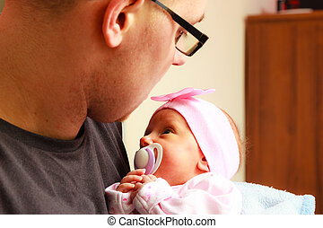 Father holding delicate his newborn baby.