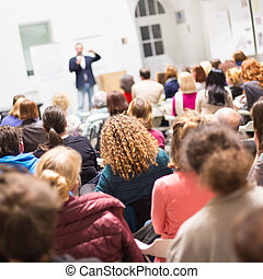 Audience in the lecture hall - Speaker Giving a Talk at...