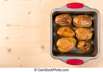 baked potatoes in tray with copy space