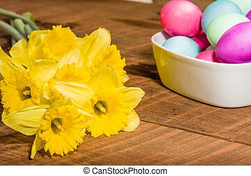 Bowl of dyed Easter eggs with daffodils