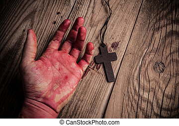 Cross in hand on wooden background