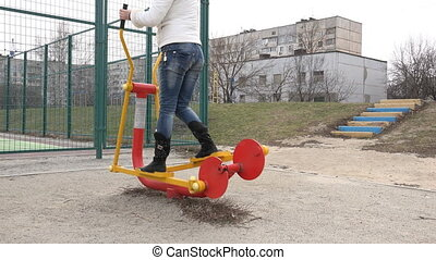 Young Women Running on Elliptical Trainer in the Open Air Gym