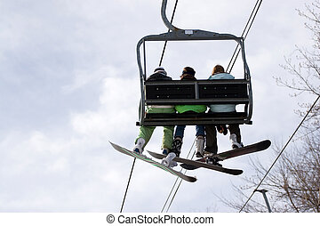 Snowboarding Ski Lift - Three snowboarder friends ride the...