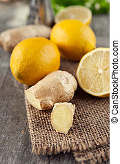 Ginger root - Fresh ginger root and lemons on old wooden...