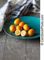 Raw kumquats - Fresh organic raw kumquats on old wooden...