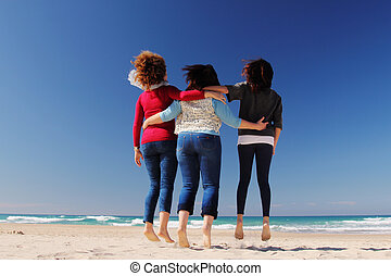 Three best friends jumping at seaside