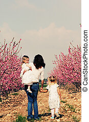 mother and daughters walking together in the park
