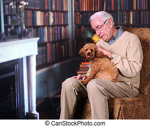 Petting Puppy - A senior man petting his poodle pup in his...