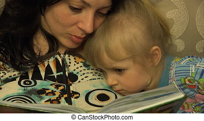 Young Mother with her Little Daughter Reading the Book Together.