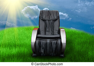 Sunny day with massage arm-chair on the grass field
