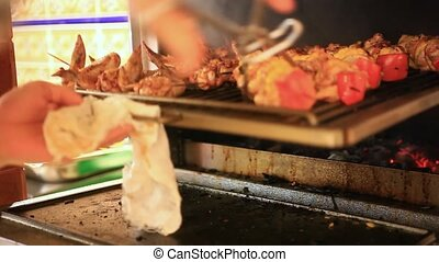 Chef checks meat skewers on readiness in Oven and close the...