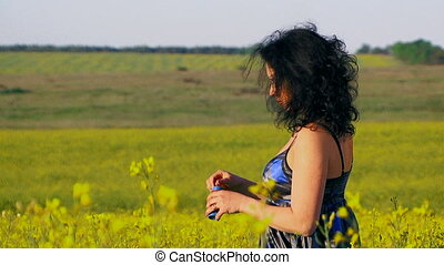 Happy woman is blowing bubbles in a field of Raps.