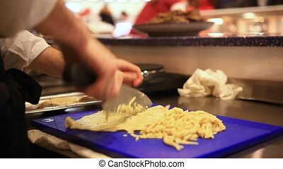Chef cutting dumpling on the board Men hands of chef making...
