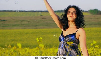 Happy woman is blowing bubbles in a field of Raps - A happy...