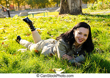 young girl laying on green grass
