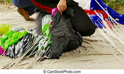 Two People Wrapping Parachute Ropes On The Ground - Shot of...