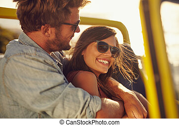 Loving young couple enjoying themselves on a road trip -...