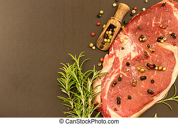 beef steak - raw beef with spices on black background