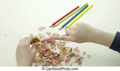 Hands sharpening a colorful pencil - A pair of child's hands...