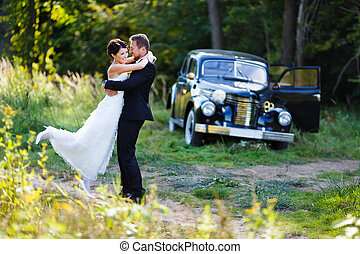 A wedding couple with old car - Embrace wedding couple on...