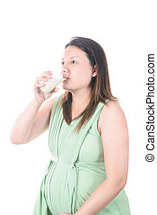 Pregnant Woman holding her pregnant belly and get a glass of...