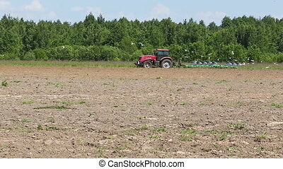 Agriculture tractor ploughing soil sping field spring