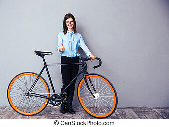 Businesswoman standing with bicycle and showing thumb up....