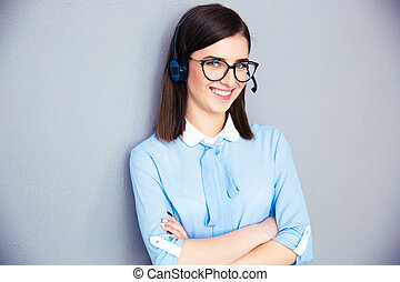 Happy businesswoman with headset and arms folded standing...