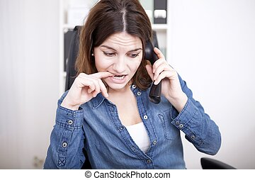 Frantic businesswoman making a phone call frowning and...