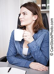 Observant young businesswoman drinking coffee at her desk...