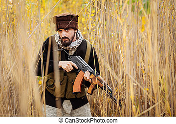 Portrait of serious middle eastern man with rifle - Portrait...