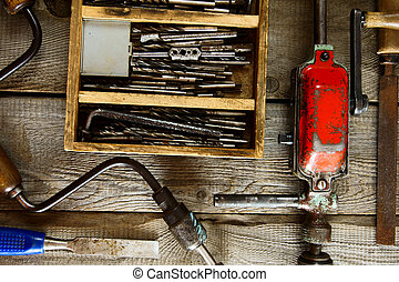 Drills in box, drill, chisel on a wooden background. - Old...