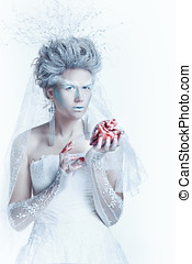 Snow queen with an unusual makeup and heart in hands -...