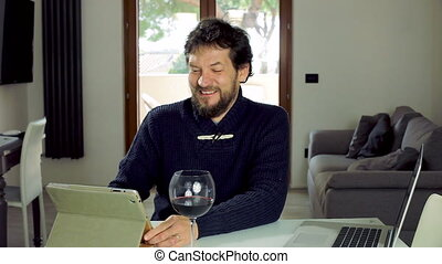 Man at home chatting with tablet - Happy man at home...