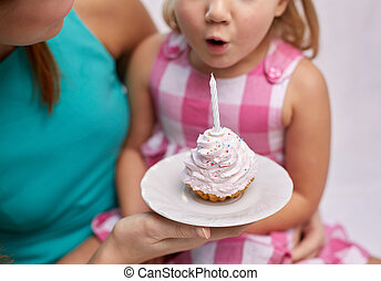 happy mother and girl blowing out cupcake candle - holiday,...