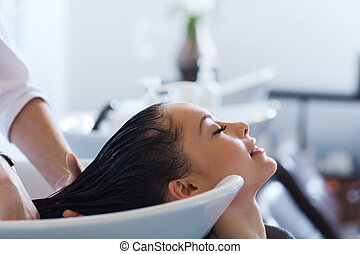 happy young woman at hair salon - beauty and people concept...