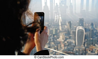 person taking aerial of London - Woman taking a snapshot...