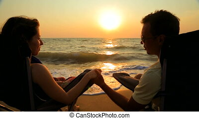 Loving Couple Holding Hands And Talking While Sitting On Outdoor Chairs At Beach