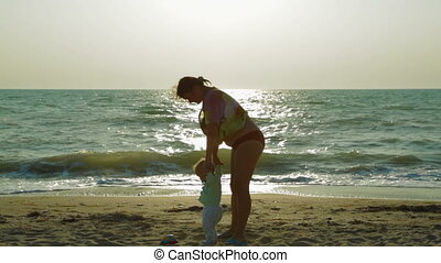 Happy Mother Spinning Her Small Baby Around At The beach -...