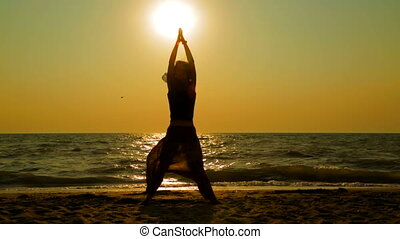Young Woman Practicing Yoga On The Beach At Sunset - Video...